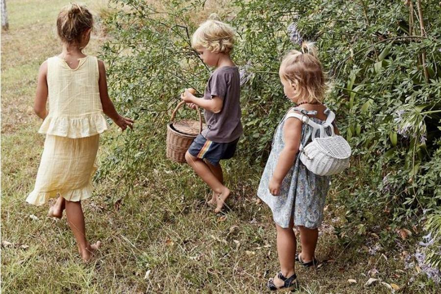 Three children walking though a field carrying baskets