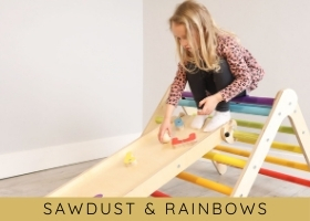 Girl playing on Sawdust & Rainbows Wee'Un, slide and ball run